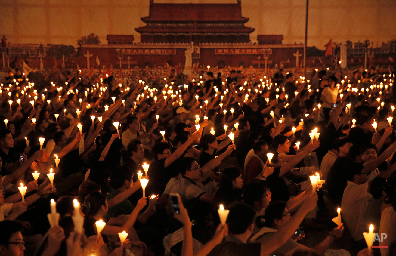 In this Thursday, June 4, 2015, photo, people attend a candlelight vigil at Victoria Park in Hong Kong. Tens of thousands of Hong Kongers joined the candlelight vigil Thursday night marking  the 1989 student-led Tiananmen Square protests. (AP Photo/Vincent Yu)