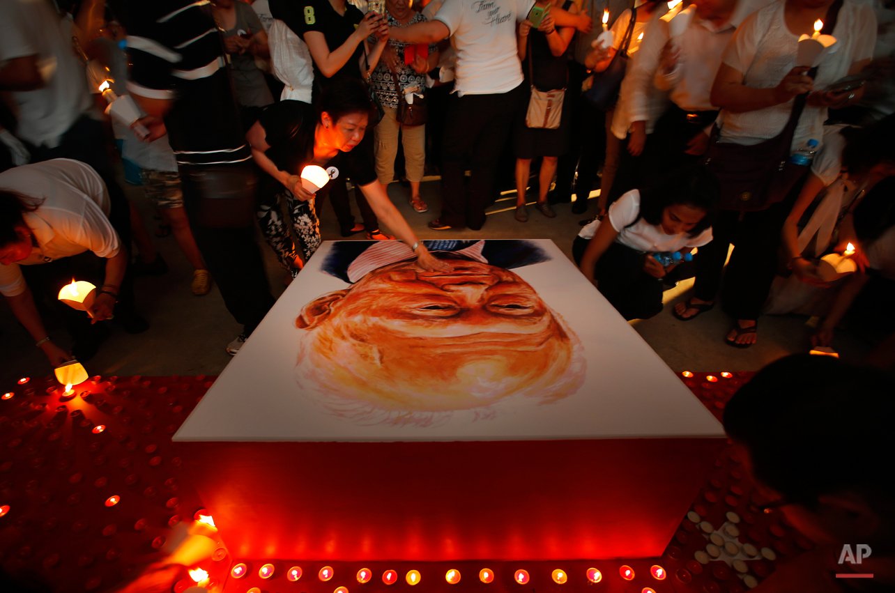 A woman touches the portrait of the late Lee Kuan Yew as others light candles as a tribute to him, Friday, March 27, 2015, in Singapore. Lee, 91, died Monday at Singapore General Hospital after more than a month of battling severe pneumonia. The government declared a week of mourning for the leader who is credited with transforming the resource-poor island into a wealthy finance and trade hub with low crime and corruption in a region saddled with graft, instability and poverty. (AP Photo/Wong Maye-E)