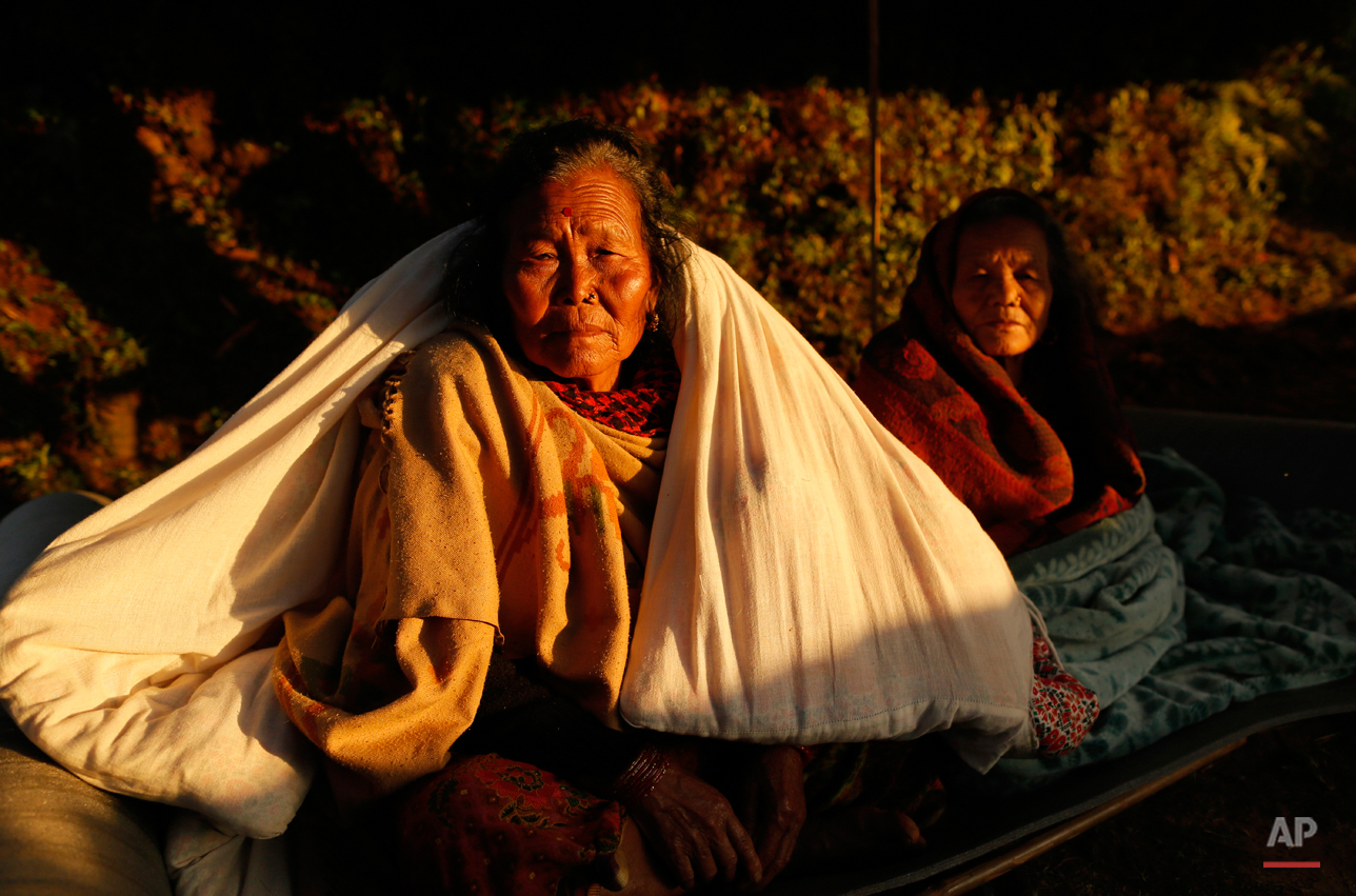 In this Tuesday, April 28, 2015, photo, two elderly women sit in the evening sun with blankets in the destroyed village of Paslang near the epicenter of Saturday's massive earthquake in the Gorkha District of Nepal. The death toll from the quake, Nepal's worst in more than 80 years, soared past 7,000 police said.  (AP Photo/Wally Santana)