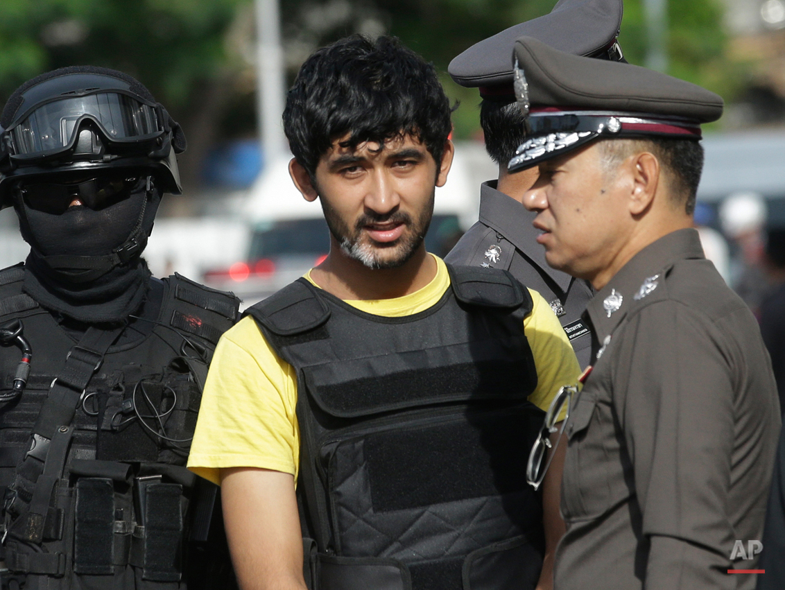Police officers escort a key suspect in last month's Bangkok bombing, yellow shirt, identified by Thai police as Yusufu Mierili, traveling on a Chinese passport, but his nationality remains unconfirmed, outside Hua Lamphong railway station during a reenactment for the Aug. 17 bombing at Bangkok's popular Erawan Shrine that left 20 people dead and more than 120 injured, Wednesday, Sept. 9, 2015. (AP Photo/Sakchai Lalit)