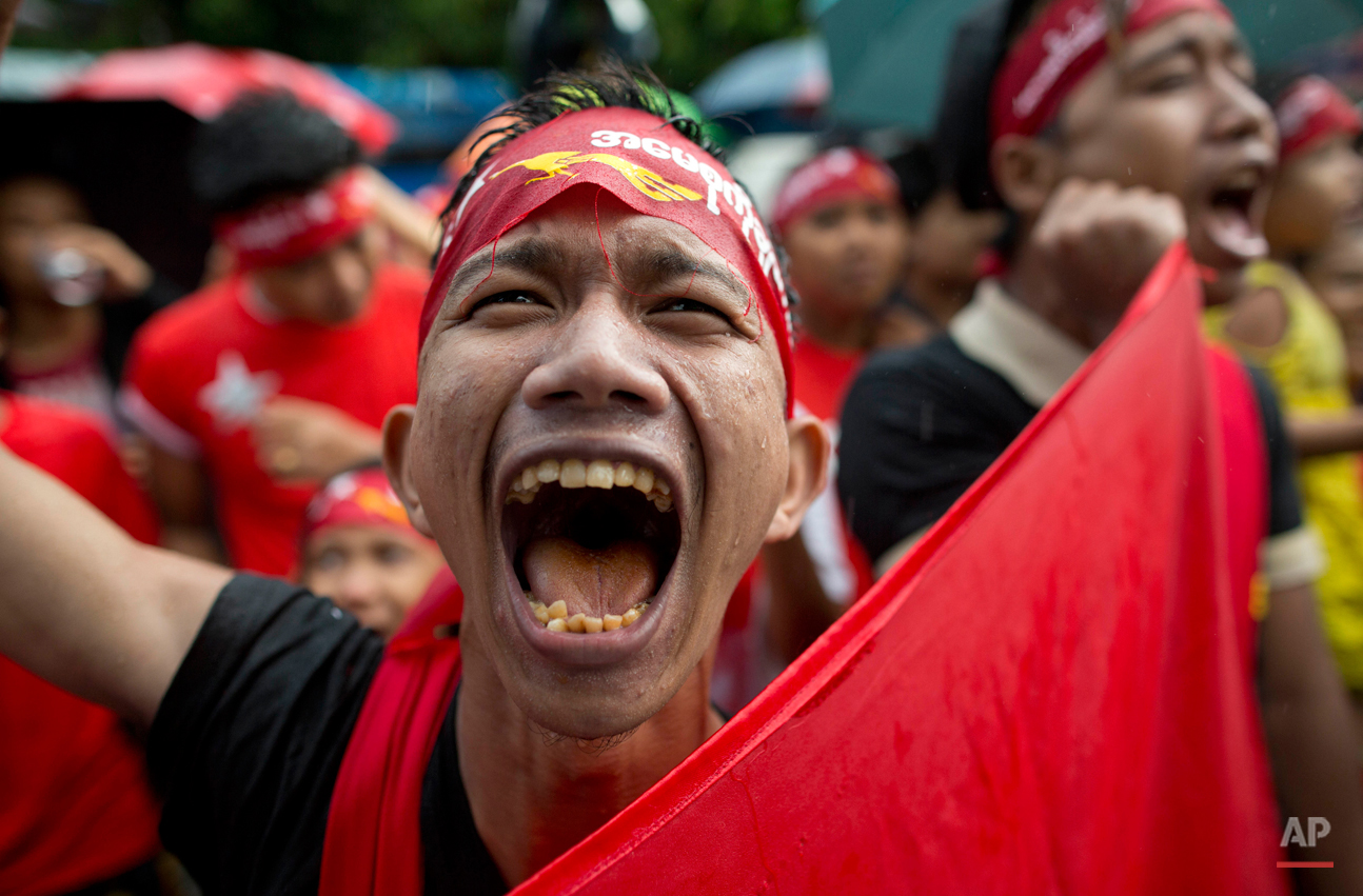 In this Monday, Nov. 9, 2015, photo, a supporter of Myanmar's National League for Democracy party braves rain outside the NLD headquarters in Yangon, Myanmar. Opposition leader Aung San Suu Kyi's NLD party was confident Monday that it was headed for a landslide victory in Myanmar's historic elections, as the democracy icon urged supporters not to provoke losing rivals who mostly represent the former junta that ruled this Southeast Asian nation for a half-century. (AP Photo/Gemunu Amarasinghe)