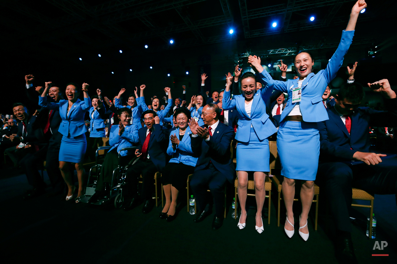 In this July 31, 2015 photo, members of the delegation from Beijing 2022 Winter Olympics candidate city react after the city was elected to host the 2022 Olympic Winter Games at IOC meeting in Kuala Lumpur, Malaysia. (AP Photo/Vincent Thian)