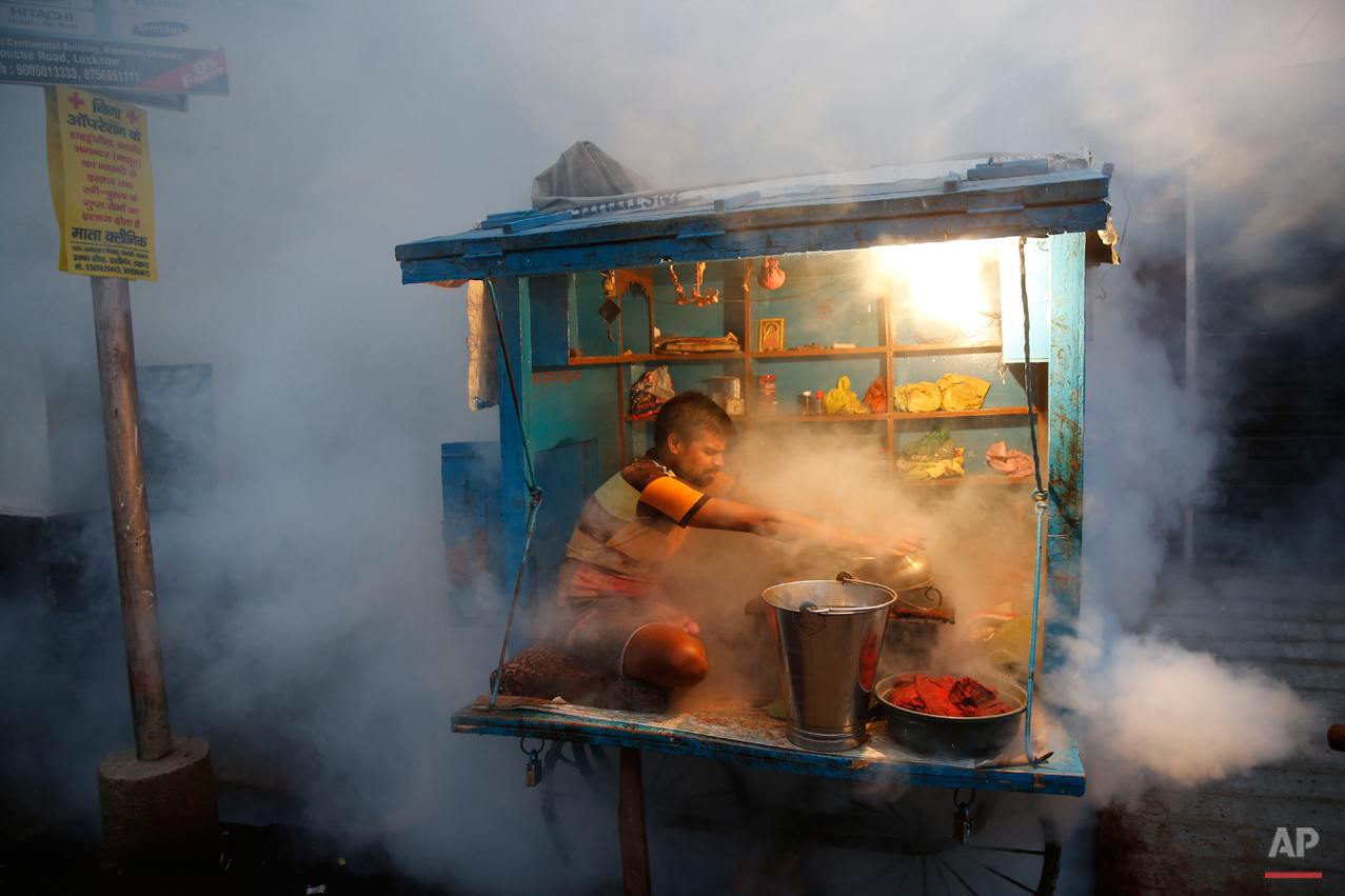 In this Tuesday, Sept. 22, 2015 photo, a man who sells chewable tobacco covers his items as a municipal worker fumigates to prevent mosquitoes from breeding in Lucknow, India. Dengue outbreaks are reported every year after the monsoon season that runs from June to September. Many people have died from the mosquito-borne disease in the country???s capital New Delhi this year. (AP Photo/Rajesh Kumar Singh)