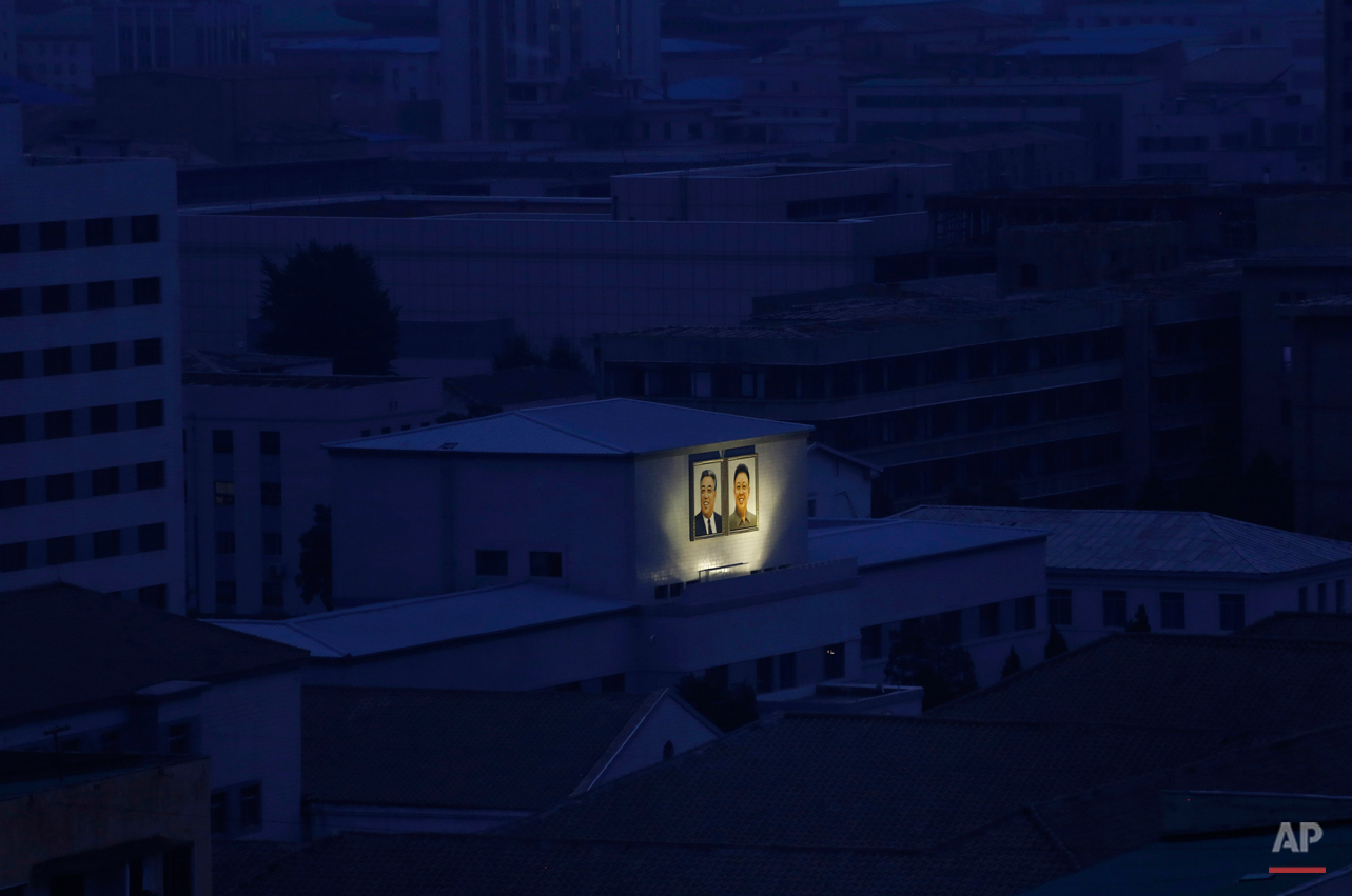 In this Aug. 19, 2015 photo, portraits of the late North Korean leaders Kim Il Sung, left, and Kim Jong Il glow on the facade of a building among others at dawn in Pyongyang, North Korea. (AP Photo/Dita Alangkara)