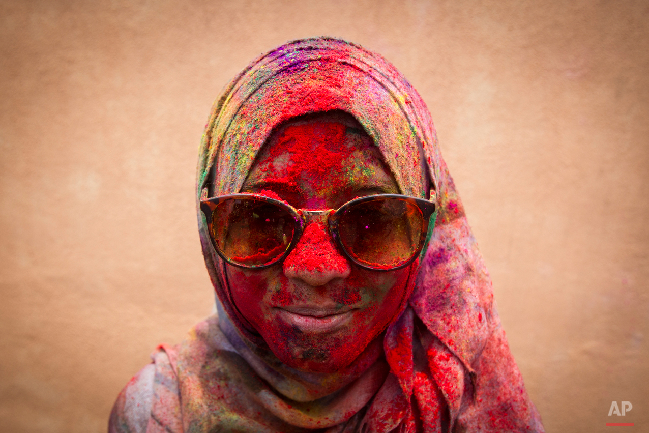 In this Saturday, March 21, 2015, photo, a Malaysian Muslim woman poses for a photo during the religious spring festival Holi in Kuala Lumpur, Malaysia. Holi, the Hindu festival of colors, is celebrated by people throwing colored powder and water at each other. (AP Photo/Joshua Paul)