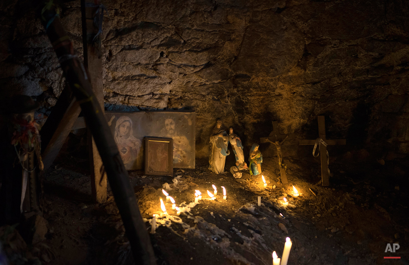 In this Nov. 1, 2015 photo, Christian icons are illuminated by candlelight inside a chapel along the Holy Sepulchre path used by pilgrims who honor Padre Cicero in Juazeiro do Norte, Brazil. People credit the late Brazilian priest with miracles and venerate him as a saint, but he's not recognized as one by the Roman Catholic Church. (AP Photo/Leo Correa)