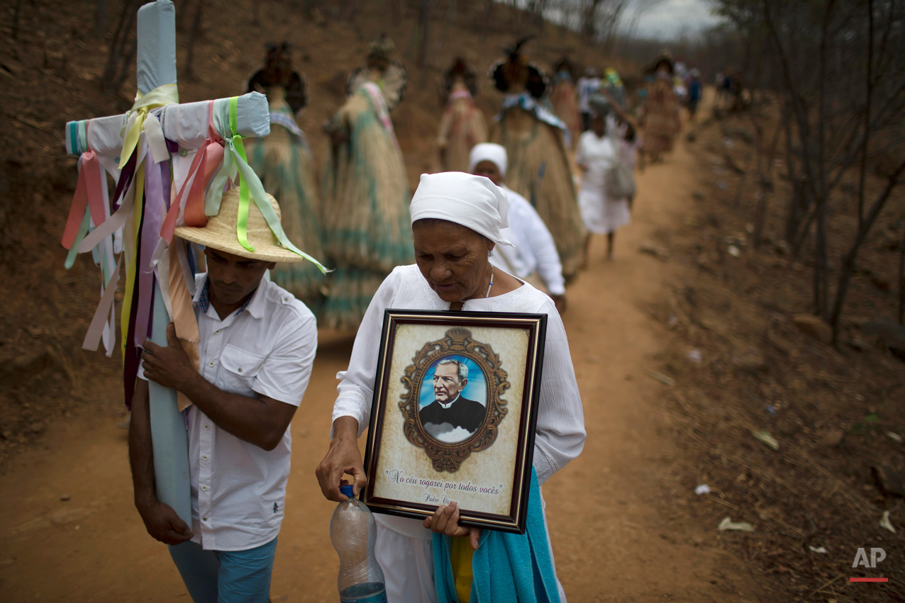 In this Oct. 31, 2015 photo, indigenous from the Pankararu tribe carry a cross and images of Padre Cicero along the Holy Sepulchre path used by pilgrims in Juazeiro do Norte, Brazil. Padre Cicero was both a priest and a politician, serving as mayor of Juazeiro do Norte for 15 years. He became renowned for helping the poor and improving the lives of farmers and residents of Brazil's arid northeast. (AP Photo/Leo Correa)