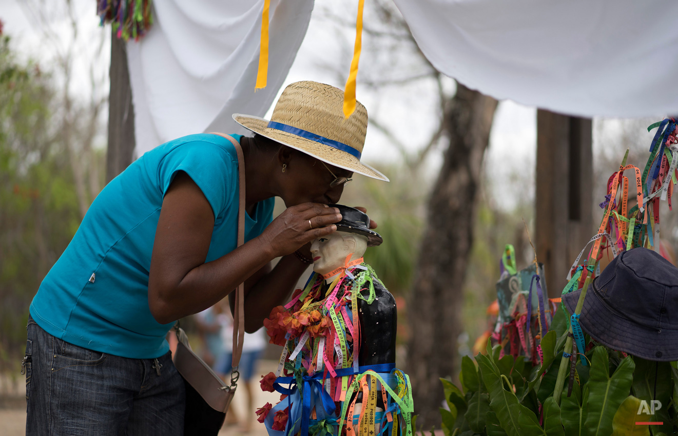 In this Oct. 31, 2015 photo, pilgrim Edite Monteiro kisses a statue of Padre Cicero standing at the start of a path called the Holy Sepulcher, used by those who come to honor the late priest in Juazeiro do Norte, Brazil. Monteiro, a 56-year-old farmer, said she came to ask for a good harvest and blessings for her family. (AP Photo/Leo Correa)