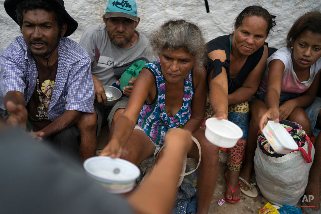 In this Oct. 31, 2015 photo, people beg for money near a statue of Padre Cicero in Juazeiro do Norte, Brazil, during a pilgrimage in honor of the late priest. The Brazilian reverend became renowned for helping the poor and improving the lives of farmers and residents of Brazil's arid northeast.  (AP Photo/Leo Correa)