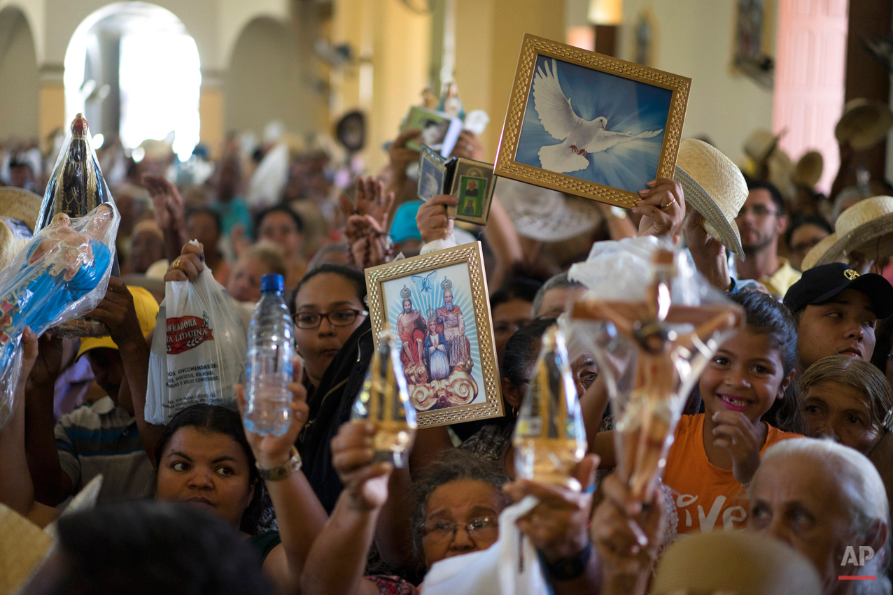 "In this Nov. 2, 2015 photo, pilgrims hold up religious icons for a blessing during the farewell ceremony at Our Lady of Sorrows church in Juazeiro do Norte, Brazil. ""We believe that he was _ that he is _ an important person for our northeast and we hope he can intercede and send rain,"" said Leunil Gomes de Carvalho, 36, from the city of Floresta, who said he has been visiting since he was 6. (AP Photo/Leo Correa)"