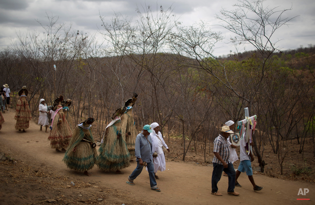 In this Oct. 31, 2015 photo, indigenous people from the Pankararu tribe walk along the Holy Sepulchre path that pilgrims use in Juazeiro do Norte, Brazil. Some wear native ceremonial outfits made of straw as others carry crosses and images of the late priest known as Padre Cicero, a figure venerated here as a saint but not recognized as one by the Roman Catholic Church. (AP Photo/Leo Correa)