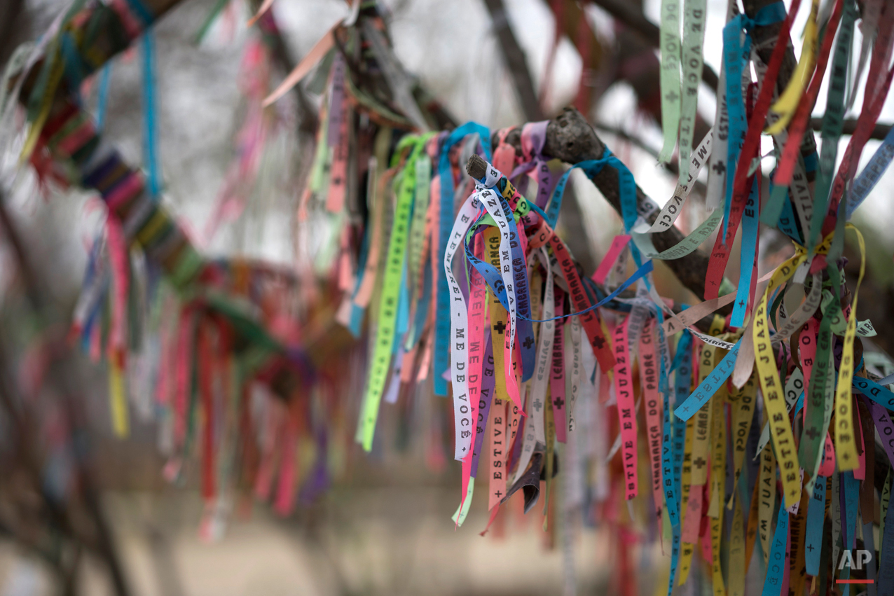 In this Oct. 31, 2015 photo, ribbons placed by pilgrims hang from trees at the start of the Holy Sepulcher path, a road used by pilgrims who walk here to honor Padre Cicero in Juazeiro do Norte, Brazil. The ribbons symbolize promises made to the late Brazilian priest. (AP Photo/Leo Correa)