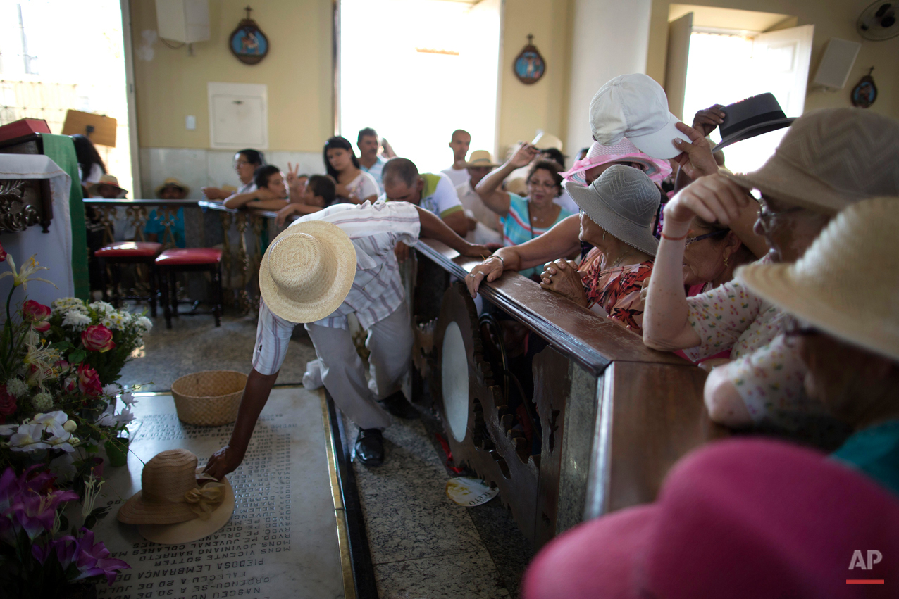 In this Oct. 30, 2015 photo, a church worker holds a pilgrim's hat over the grave of Padre Cicero to bless it at Our Lady of Perpetuo Socorro church in Juazeiro do Norte, Brazil. Followers of the late Rev. Cicero Romao Batista, who hold him up as worthy of sainthood, have transformed this town into a place of pilgrimage, one of the leading centers of popular religiosity in Latin America with hundreds of thousands of visitors each year. (AP Photo/Leo Correa)