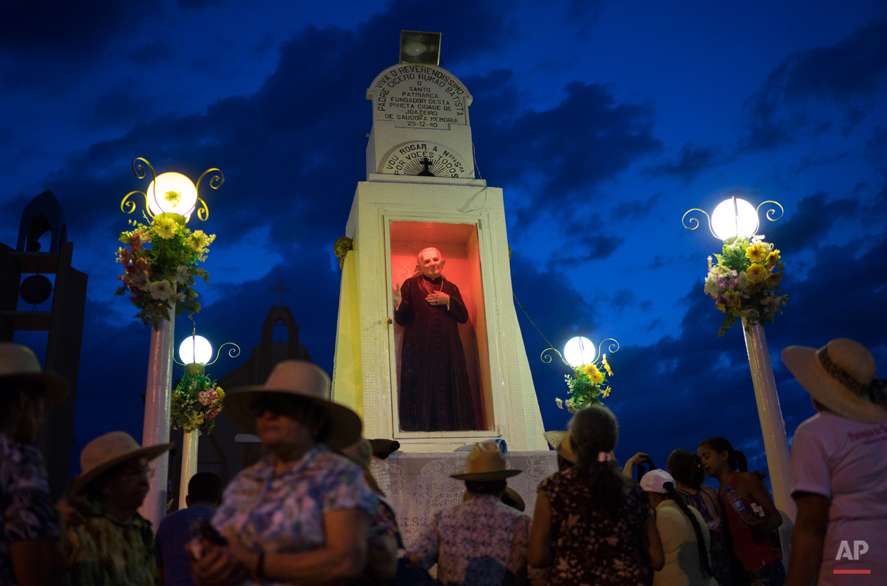In this Oct. 30, 2015 photo, pilgrims pray and pay tribute at a statue of Padre Cicero at the public square in Juazeiro do Norte, Brazil. The Rev. Cicero Romao Batista was born in 1844 and died at age 90 in this arid, impoverished part of northeast Brazil. His followers say that during a Mass celebrated by the priest in 1889, a woman receiving communion declared that the Host had turned to blood in her mouth. People called it a miracle, but the Vatican was displeased and suspended him. (AP Photo/Leo Correa)