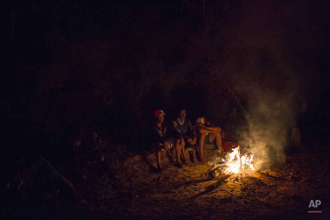 Residents sits by a bonfire after evacuating their houses at the small town of Bento Rodrigues after a dam burst on Thursday, in Minas Gerais state, Brazil, Friday, Nov. 6, 2015.(AP Photo/Felipe Dana)