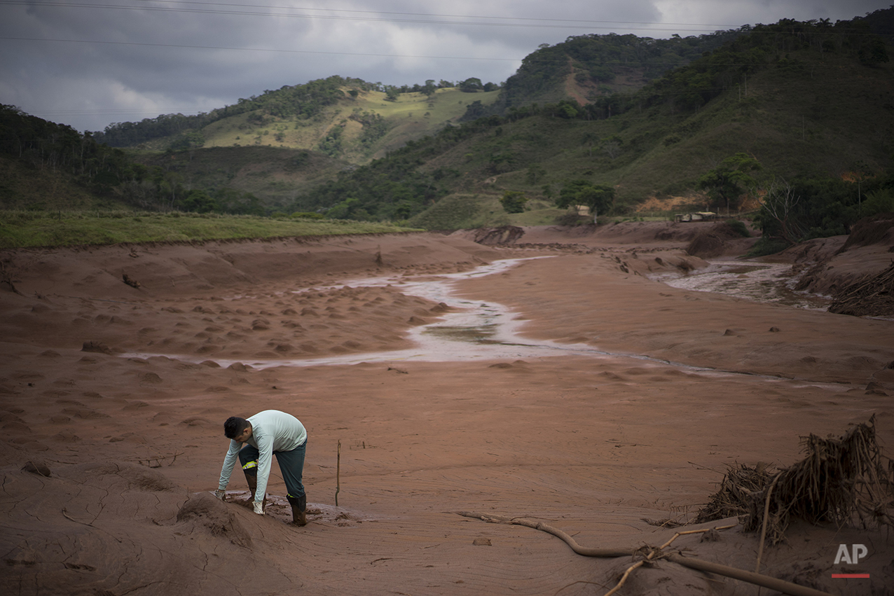 An electricity worker attempts to cross a flooded area in Barra Longa after a dam burst on Thursday in Minas Gerais state, Brazil, Saturday, Nov. 7, 2015. (AP Photo/Felipe Dana)