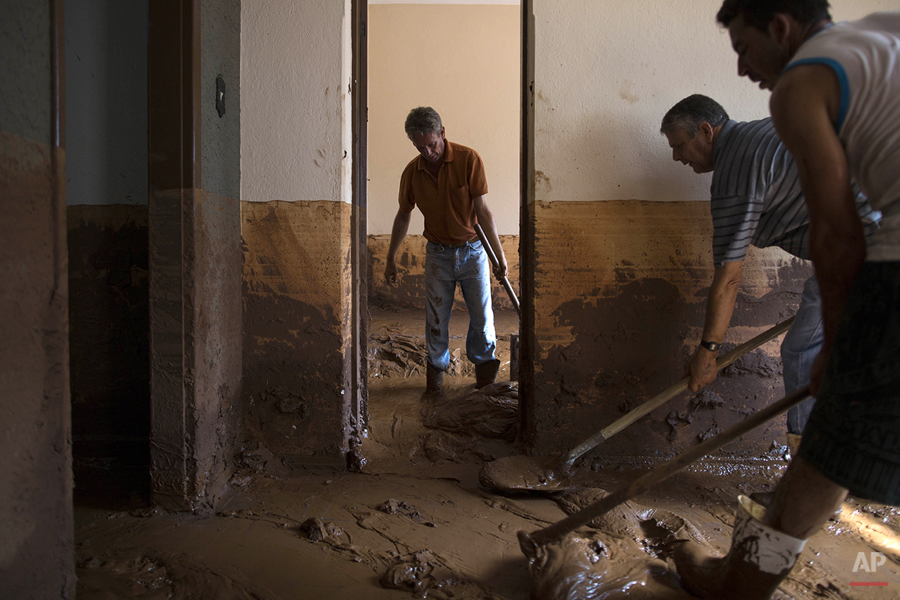 People remove mud from a damaged home in Barra Longa after a dam burst on Thursday in Minas Gerais state, Brazil, Saturday, Nov. 7, 2015. (AP Photo/Felipe Dana)