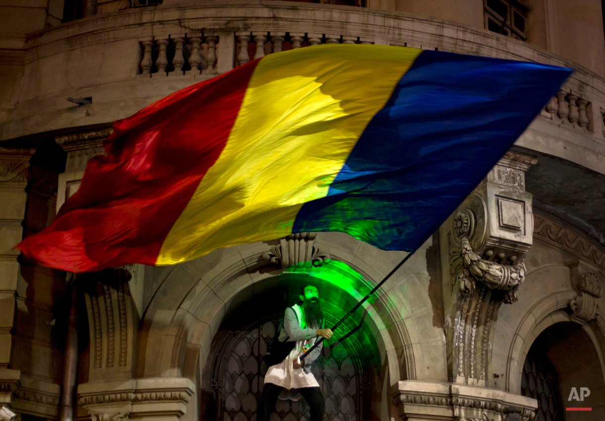 A man's face is illuminated by a laser torch as he waves a large Romanian flag, after climbing the University building, during the third day of protests, joined by tens of thousands across the country, calling for early elections, in Bucharest, Romania, Thursday, Nov. 5, 2015. Romania's President Klaus Iohannis has named the Education Minister Sorin Campeanu as interim premier following the resignation of the Prime Minister Victor Ponta and his cabinet. (AP Photo/Vadim Ghirda)