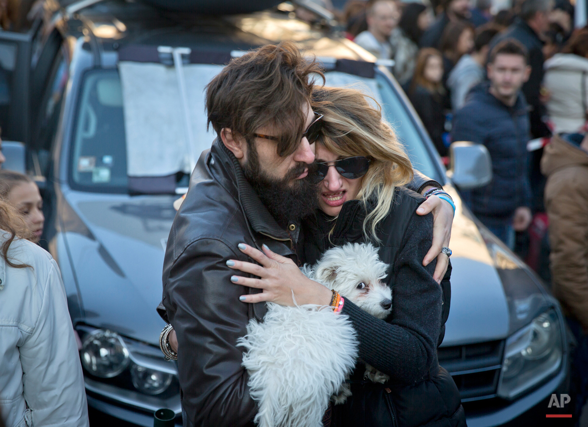 A woman cries as her partner comforts her outside the Colectiv nightclub, during a mourning march joined by thousands in Bucharest, Romania, Sunday, Nov. 1, 2015. As the nation entered its second day of mourning, thousands paid their respects at the Colectiv nightclub in Bucharestís 4th district, scene of mayhem and tragedy Friday night when a fire engulfed the venue, causing a panic that killed tens of people and injured many others, raising serious questions about fire regulations and safety procedures in Romania. (AP Photo/Vadim Ghirda)