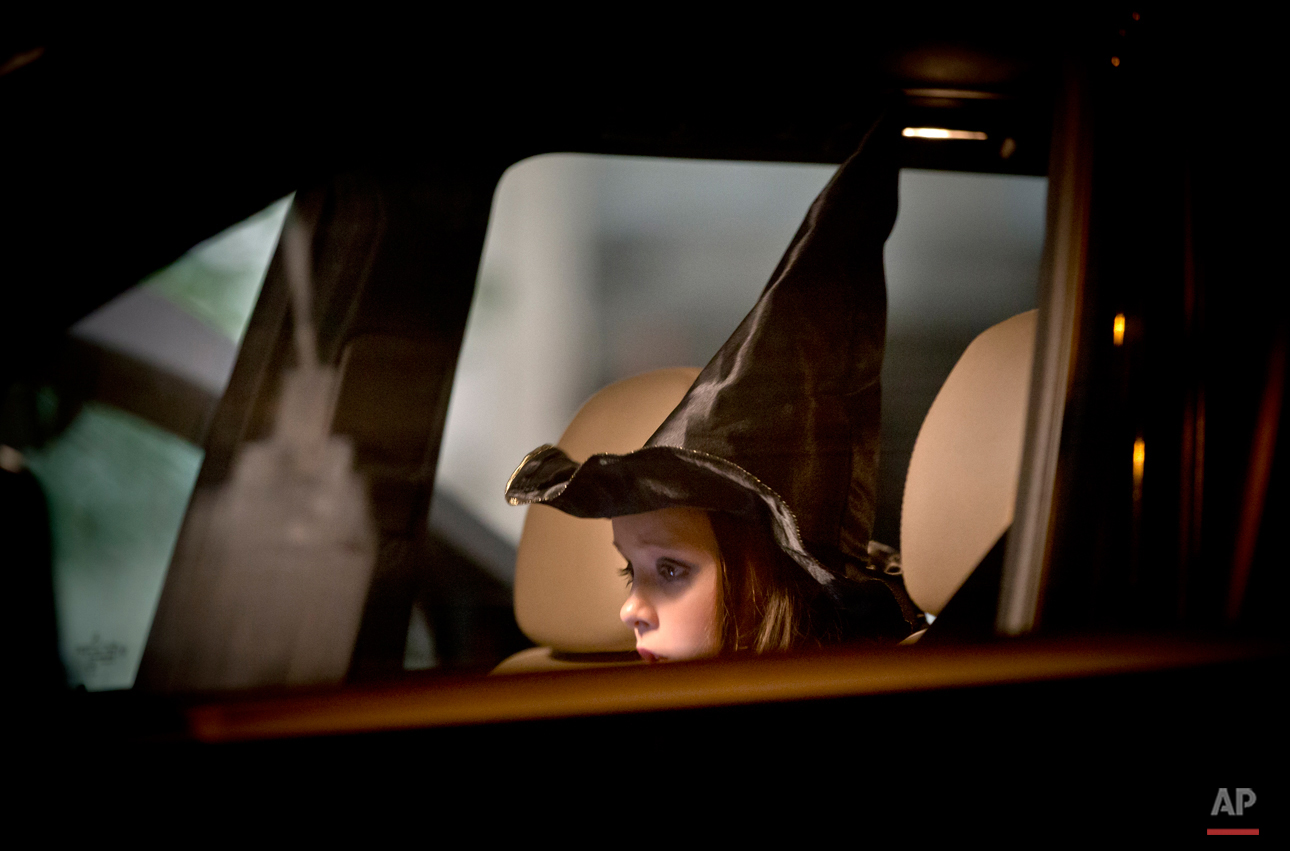 A child wears a Halloween hat sits in a vehicle, as the adults accompanying her light candles and lay flowers outside the compound that housed the nightclub where a fire occurred in the early morning hours in Bucharest, Romania, Saturday, Oct. 31, 2015. Hundreds of young people had gone clubbing at the hip Colectiv nightclub Friday night to enjoy a free concert by the Goodbye to Gravity metal band but the evening ended in horror, as the inferno caused a panic that killed tens of people and injured many others.(AP Photo/Vadim Ghirda)