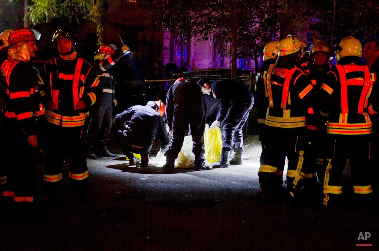 Forensic workers collect items outside the site of a fire that occurred in a club in Bucharest, early Saturday, Oct. 31, 2015. A heavy metal band's pyrotechnical show sparked a deadly fire Friday at a Bucharest nightclub, killing more than 20 people and injuring scores of the club's mostly youthful patrons, officials and witnesses said. (AP Photo/Vadim Ghirda)