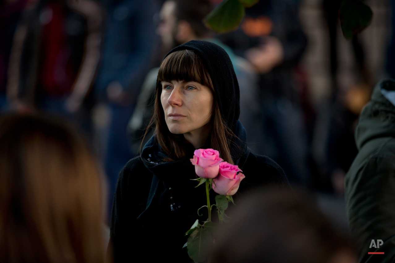 A woman holds roses while standing outside the Colectiv nightclub during a mourning march joined by thousands pauses in Bucharest, Romania, Sunday, Nov. 1, 2015. As the nation entered its second day of mourning, thousands paid their respects at the Colectiv nightclub in Bucharestís 4th district, scene of mayhem and tragedy Friday night when a fire engulfed the venue, causing a panic that killed tens of people and injured many others, raising serious questions about fire regulations and safety procedures in Romania. (AP Photo/Vadim Ghirda)
