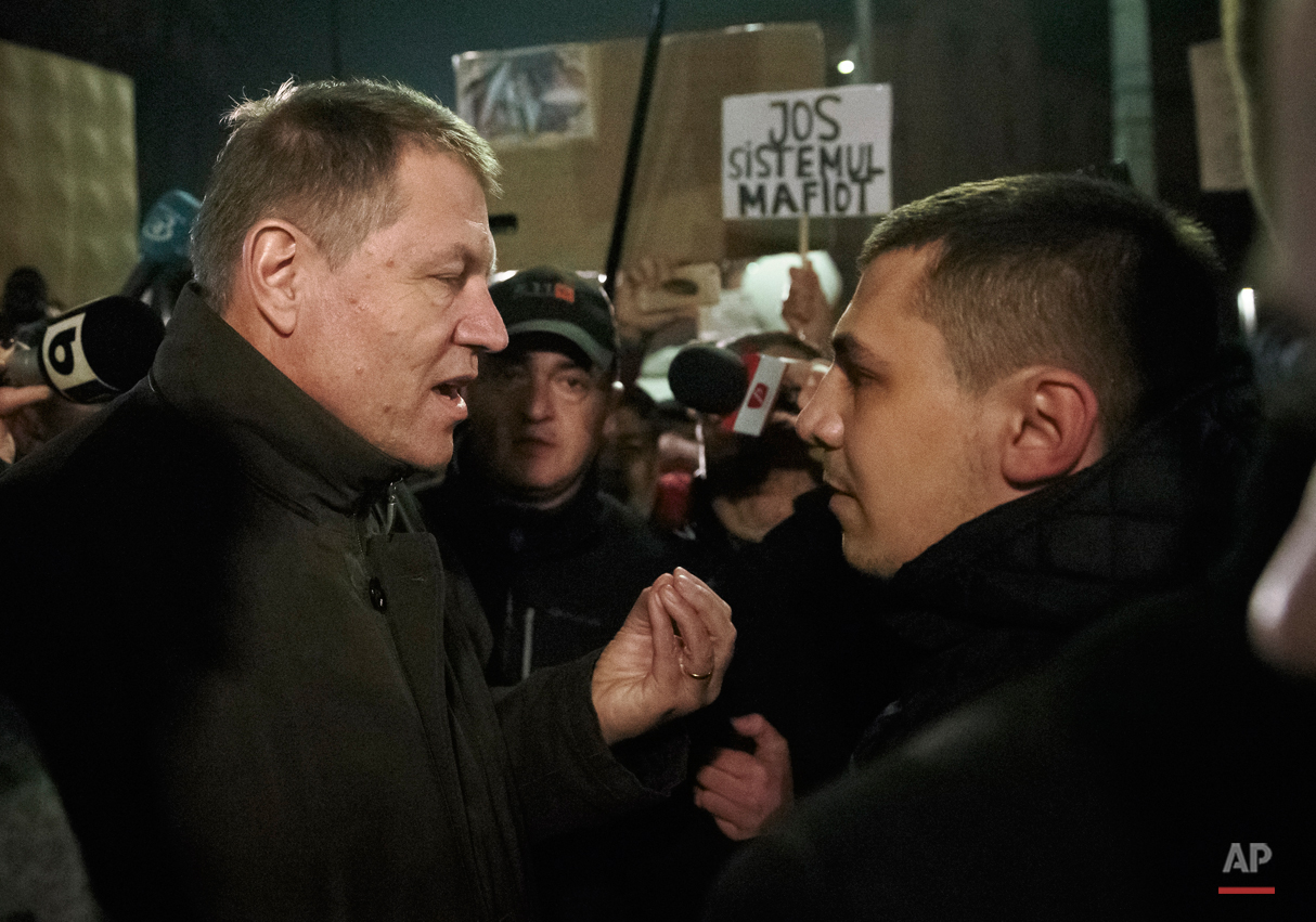 Romanian President Klaus Iohannis speaks to a protester in University Square, the staging area for protests calling for better governance and an end to corruption, in Bucharest, Romania, Sunday night, Nov. 8, 2015. People power has ousted the Romanian government, which resigned after demonstrations over a nightclub fire causing more than 40 deaths, but it isnít the first time a popular movement has shaken the government, and based on their past experiences many Romanians are skeptical that the leaderless street movement will succeed in doing away with the old order. (AP Photo/Vadim Ghirda)