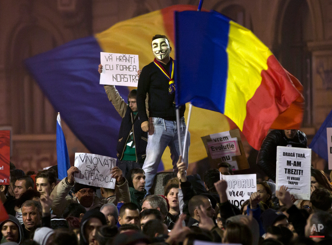"""A man wearing a Guy Fawkes mask stands above protesters shouting slogans against the Romanian politicians during the fourth day of protests, joined by tens of thousands across the country, calling for early elections, in Bucharest, Romania, Friday, Nov. 6, 2015.  Large street protests followed the Oct. 30 nightclub fire, which many Romanians blame on a weak enforcement of regulations and corruption. The street protesters have condemned the nationís politicians as arrogant and corrupt and isolated from the problems of ordinary people. Banners read"""" You are feeding on our hunger,"""" top left, """"The culprits must pay,"""" bottom left, and """" not even you are above the law: in reference to politicians,"""" far right bottom. (AP Photo/Vadim Ghirda)"""