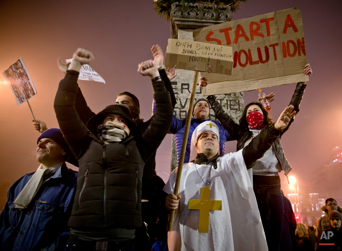 Protesters, one wearing an outfit mocking Orthodox Patriarch Daniel, shout slogans against the Romanian politicians during the fourth day of protests, joined by tens of thousands across the country, calling for early elections, in Bucharest, Romania, Friday, Nov. 6, 2015.  Protesters calling for an end to alleged widespread corruption have turned their anger to the powerful and rich Romanian Orthodox Church, asking for it's financial privileges to be reviewed, with public discontent with the church at an all-time high after it failed to address an outpouring of national grief in the wake of a nightclub fire which left more than 30 dead.(AP Photo/Vadim Ghirda)
