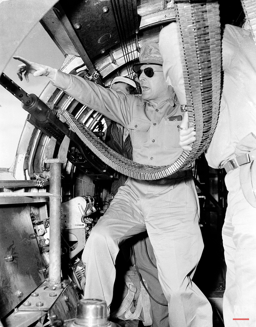 In this image provided by the U.S. Army Signal Corps, U.S. Gen. Douglas MacArthur observes a military operation from a B-17 Flying Fortress gun port on Sept. 5, 1943 during World War II.  In the exercise, 1,500 paratroopers landed in Markham Valley near Nadzab to entrap Japanese forces at Lae and Salamaua section in New Guinea.  (AP Photo/U.S. Army Signal Corps)