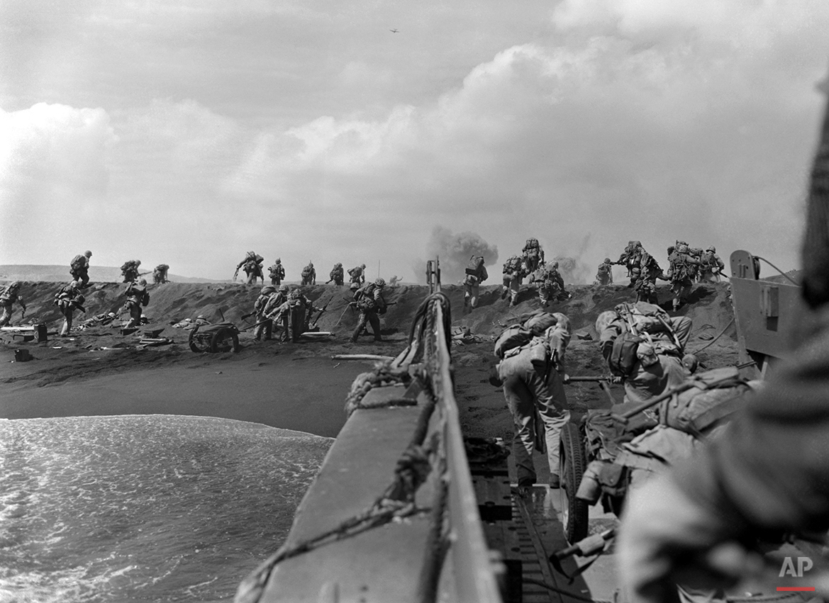 In the Pacific theater of World War II, U.S. Marines hit the beach and charge over a dune on Iwo Jima in the Volcano Islands Feb. 19, 1945, the start of one of the deadliest battles of the war against Japan. (AP Photo/Joe Rosenthal)