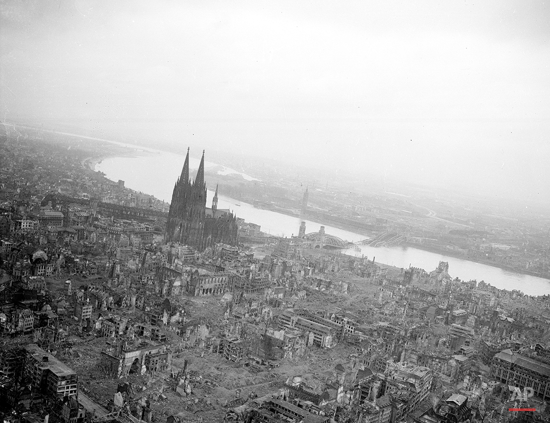 This aerial view shows the destruction of the German city of Cologne caused by Allied air warfare against Nazi Germany during World War II.  The Cologne Cathedral, which suffered blast and shell damage, stands erect on the west bank of the Rhine river on March 12, 1945.  At right, half submerged in the waters of the Rhine is the Hohenzollern Bridge.  (AP Photo/William C. Allen)