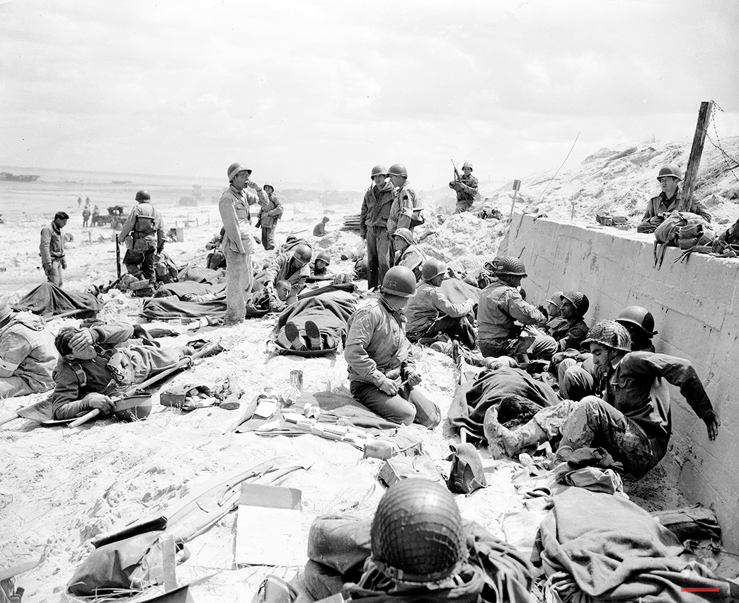 American soldiers lie on stretchers and sit propped against a sea wall awaiting transportation back to England for treatment after being wounded in the Normandy invasion, northern France, June 1944 during World War II.  (AP Photo/Peter J. Carroll)