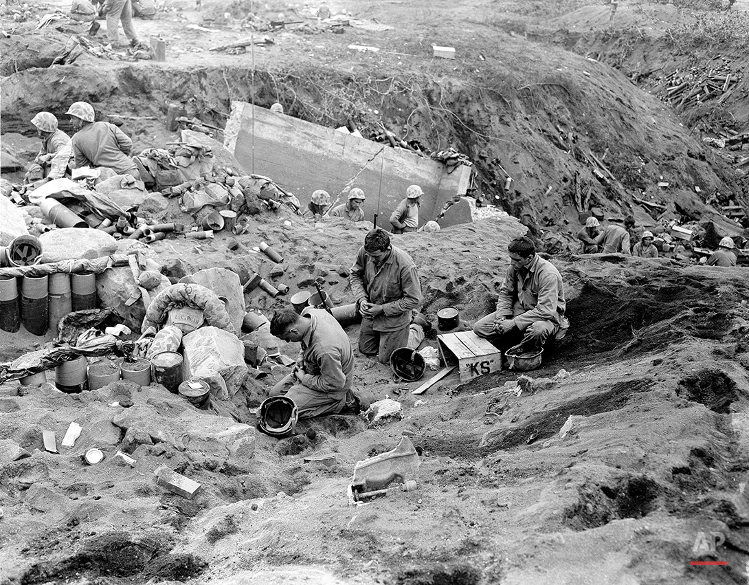 U.S. Marines kneel in prayer before they receive communion during a pause in the fighting for Motoyam Airstrip No. 1 on Iwo Jima, Volcano Island of Japan, March 1, 1945 in World War II.  The soldiers, from left are , Pfc. Edmond L. Fadel, Niagara Falls, N.Y.; Pvt. Walter M. Sokowski, Syracuse, N.Y.; and Pvt. Nicholas A. Zingaro, Syracuse, N.Y.  (AP Photo/Joe Rosenthal)