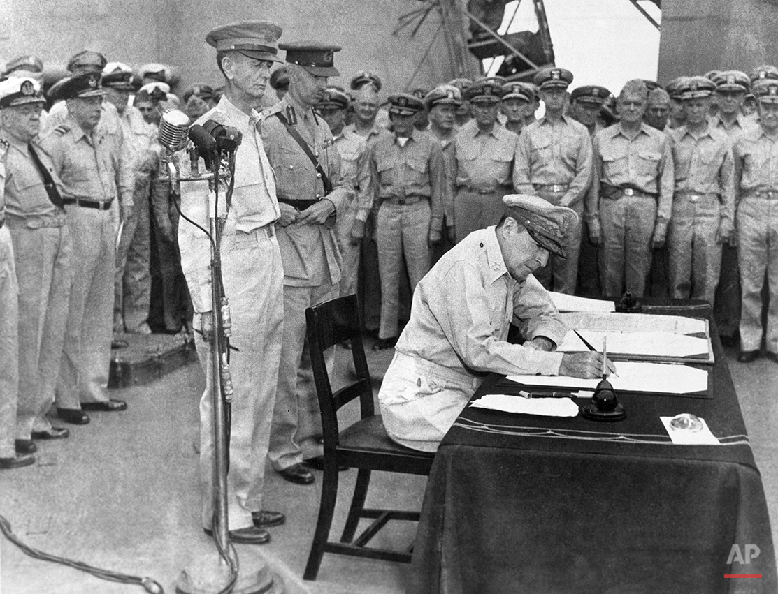 U.S. Gen. Douglas MacArthur signs the Japanese surrender documents, Sept. 2, 1945, aboard the USS Missouri in Tokyo Bay, formally ending World War II. Standing  behind him are Lt. Gen. Jonathan Wainwright, left foreground, who surrendered Bataan to the Japanese, and British Lt. Gen. A. E. Percival, next to Wainwright, who surrendered Singapore, as they witness the ceremony with other American and British officers. (AP Photo/Frank Filan)