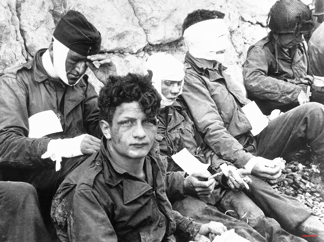 A group of American assault troops who stormed Normandy, France take time out for food on June 8, 1944. (AP Photo)