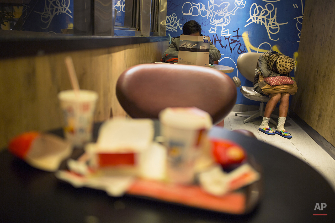 "In this Oct. 29, 2015 photo, a woman sleeps with her belongings at night in a 24-hour McDonald's branch in Hong Kong. The recent death of a woman at a Hong Kong McDonald's, where her body lay slumped at a table for hours unnoticed by other diners, has focused attention on the city's working poor and homeless people, dubbed ""McRefugees,"" who spend their nights at the fast food outlet's 24-hour branches. (AP Photo/Vincent Yu)"
