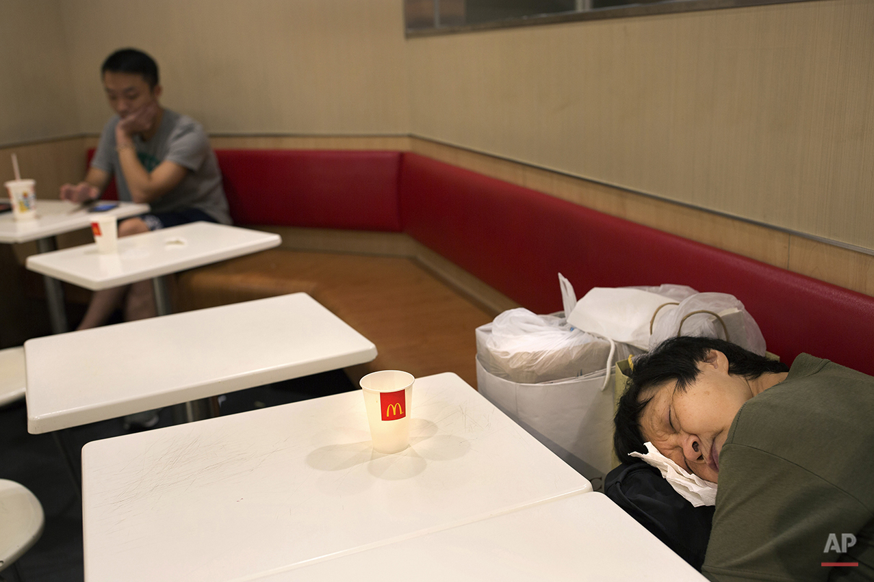 "In this Oct. 30, 2015 photo, a woman sleeps with her belongings at night in a 24-hour McDonald's branch in Hong Kong. The recent death of a woman at a Hong Kong McDonald's, where her body lay slumped at a table for hours unnoticed by other diners, has focused attention on the city's working poor and homeless people, dubbed ""McRefugees,"" who spend their nights at the fast food outlet's 24-hour branches. (AP Photo/Vincent Yu)"