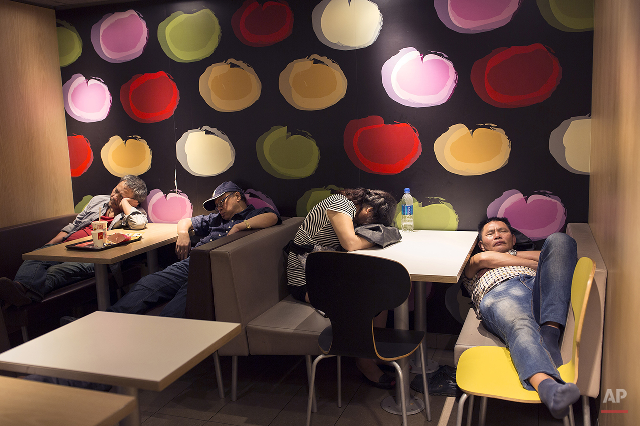 "In this Oct. 30, 2015 photo, a group of people sleep at night in a 24-hour McDonald's branch in Hong Kong. The recent death of a woman at a Hong Kong McDonald's, where her body lay slumped at a table for hours unnoticed by other diners, has focused attention on the city's working poor and homeless people, dubbed ""McRefugees,"" who spend their nights at the fast food outlet's 24-hour branches. (AP Photo/Vincent Yu)"