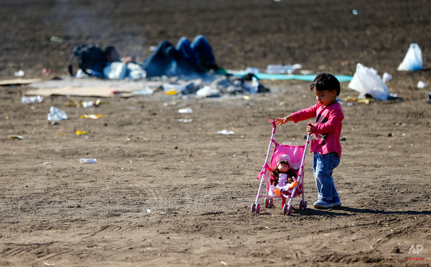 In this photo taken on Wednesday, Sept. 9, 2015, a young girl plays on a field as she waits in a camp near the border line between Serbia and Hungary in Roszke, southern Hungary. Among the hundreds of thousands of migrants making their way to Europe, there are many families whose young children still play or find something to smile about even after harrowing experiences and long journeys. (AP Photo/Matthias Schrader)