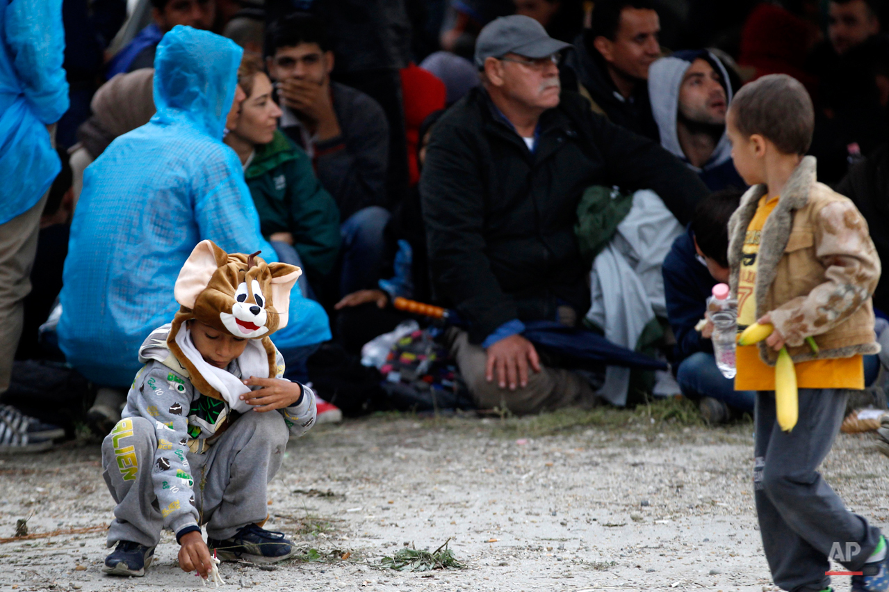 In this photo taken on Thursday, Sept. 24, 2015, young boy play, after  a group of migrants crossed the border with Croatia arriving in Barcs, Hungary. Among the hundreds of thousands of migrants making their way to Europe, there are many families whose young children still play or find something to smile about even after harrowing experiences and long journeys. (AP Photo/Petr David Josek)
