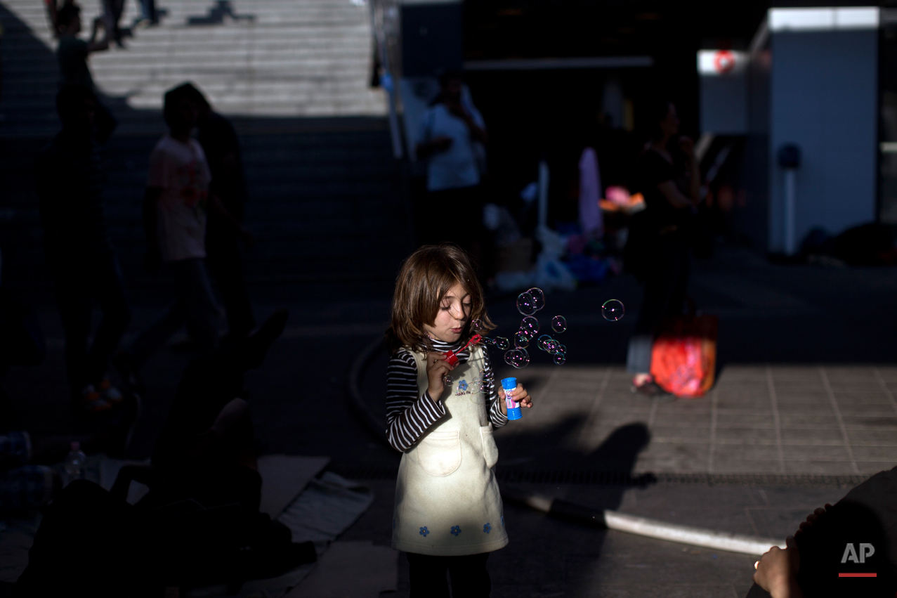 In this photo taken on Friday, Sept. 4, 2015, a girl blows soap bubbles at the Keleti train station in Budapest, Serbia. Among the hundreds of thousands of migrants making their way to Europe, there are many families whose young children still play or find something to smile about even after harrowing experiences and long journeys. (AP Photo/Marko Drobnjakovic)