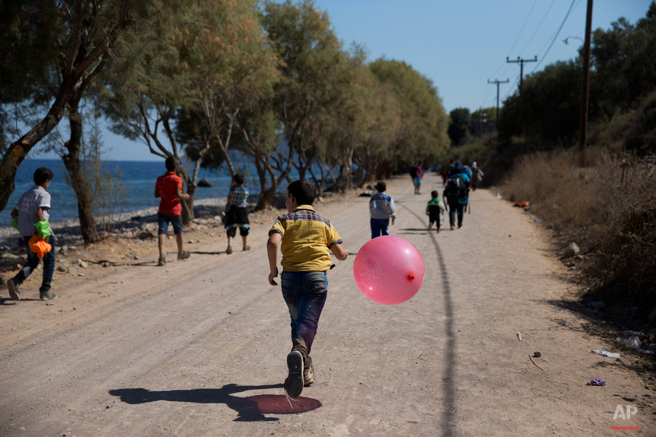 In this picture taken on Saturday, Sept. 19, 2015, a Syrian boy holding a balloon runs after he arrived with his family from Turkey, to the shores of the Greek  island of Lesbos, on an inflatable dinghy. Children are resourceful and find joy and distraction for hours in simple objects. Their parents often carry everything they still own in a backpack or two, making dolls and Lego blocks an impossible luxury. (AP Photo/Petros Giannakouris)