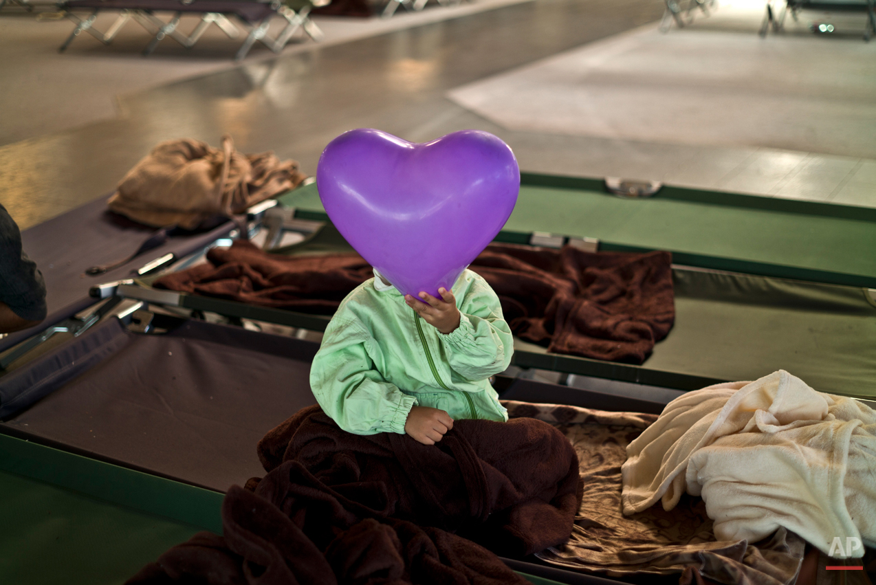 In this photo taken on Tuesday, Sept. 22, 2015, an Afghan refugee child covers his face with a balloon while he and other migrants spent the night in a shelter near Graz, Austria. Children are resourceful and find joy and distraction for hours in simple objects. Their parents often carry everything they still own in a backpack or two, making dolls and Lego blocks an impossible luxury. (AP Photo/Muhammed Muheisen)