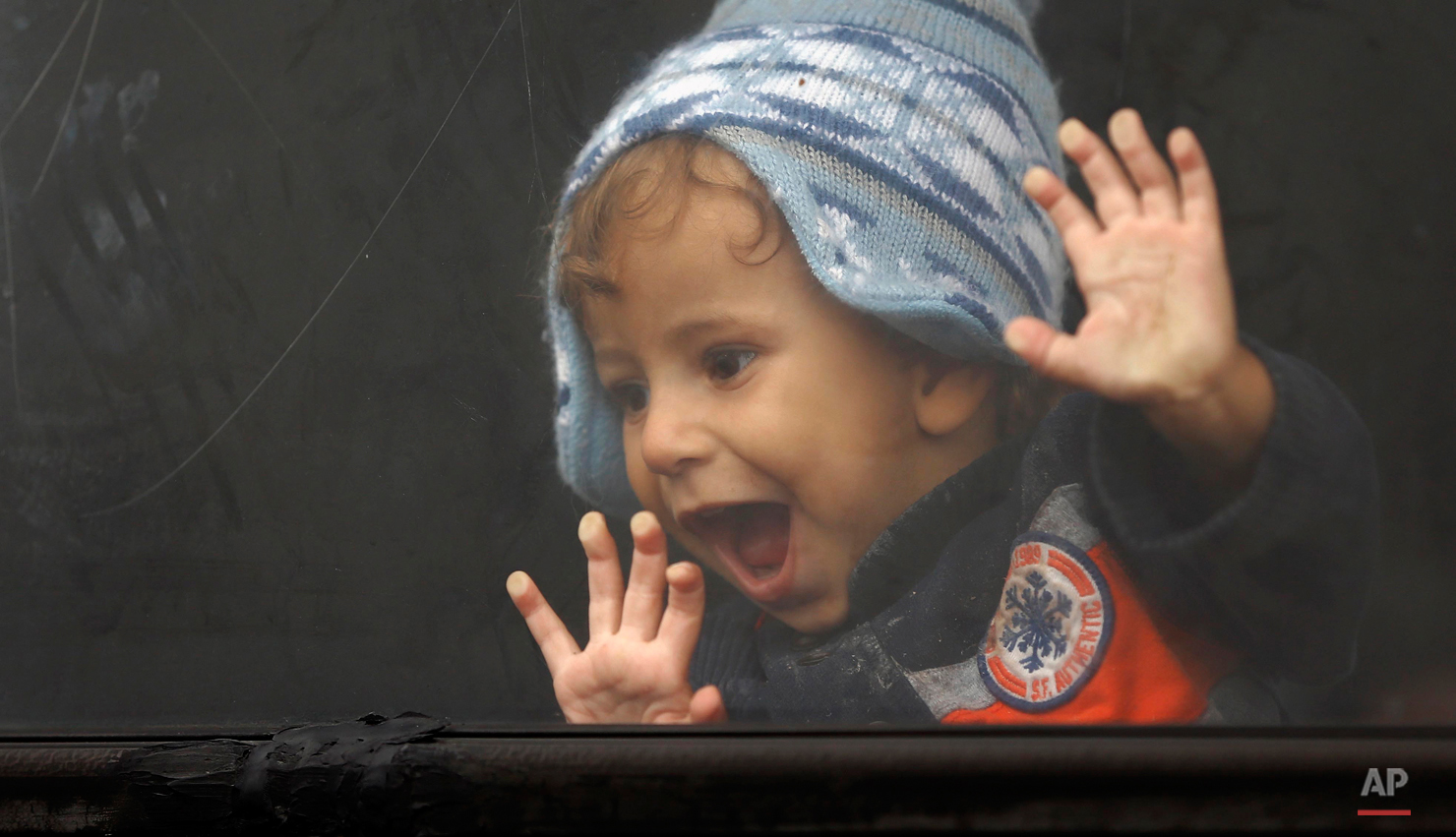 In this photo taken on Friday, Sept. 11, 2015, a young child laughs, looking out of a bus window in a center for asylum seekers near Roszke, southern Hungary. Among the hundreds of thousands of migrants making their way to Europe, there are many families whose young children still play or find something to smile about even after harrowing experiences and long journeys. (AP Photo/Matthias Schrader)