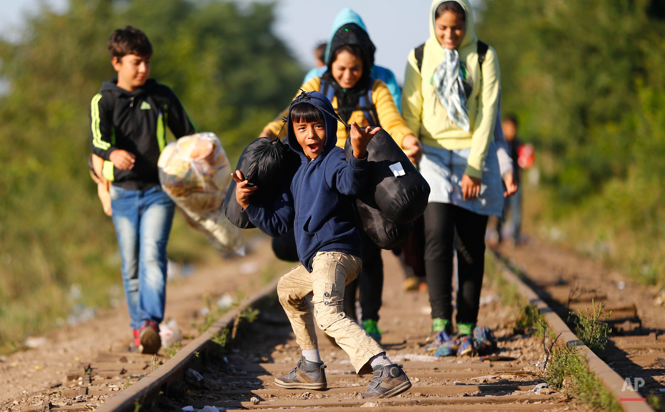 In this photo taken on Wednesday, Sept. 9, 2015, a young migrant boy jokes as he crosses the Hungarian-Serbian border with his family near Roszke, southern Hungary. Among the hundreds of thousands of migrants making their way to Europe, there are many families whose young children still play or find something to smile about even after harrowing experiences and long journeys. (AP Photo/Matthias Schrader)