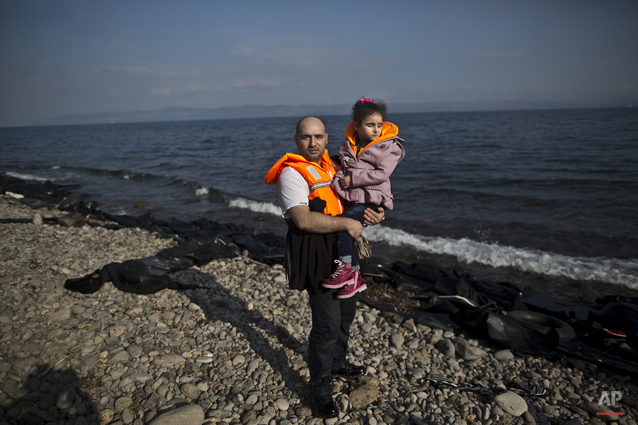 """In this photo taken on Saturday, Oct. 3, 2015, Syrian refugee Mahmoud Naoura, 30, who came from Aleppo, Syria, poses for a picture while holding his daughter Huda, 5, who was injured in 2012 by a government bombing on their home which made her lose her sight, shortly after arriving on a dinghy from the Turkish coast to the northeastern Greek island of Lesbos. Naoura said """"I just want to cure my daughter. Huda will see again, inshallah, and when she will open her eyes I want her to see a safe environment around."""" (AP Photo/Muhammed Muheisen)"""