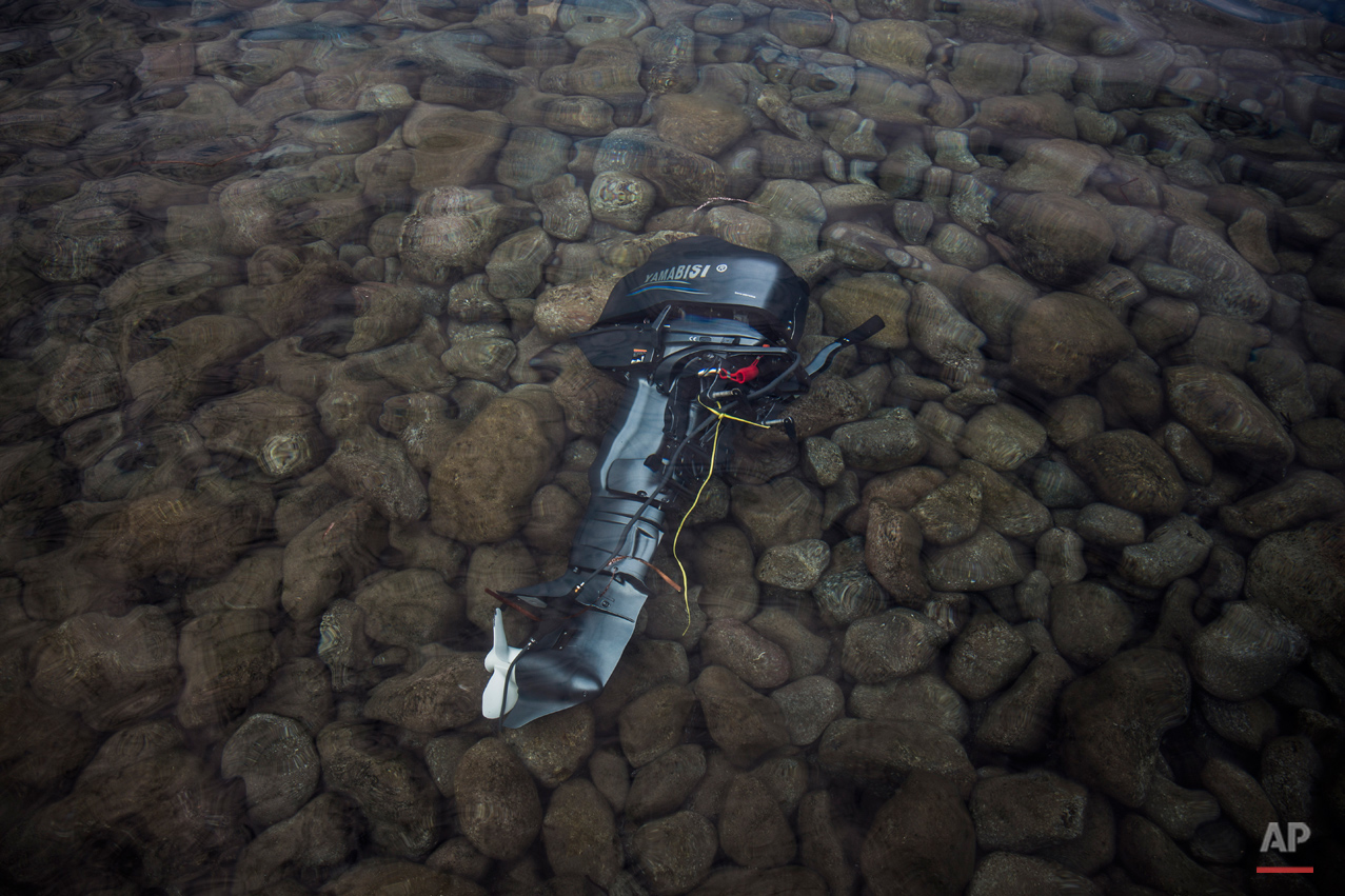 In this Wednesday, Oct. 7, 2015 photo, the engine of a boat used by refugees to travel from the Turkish coast to the northeastern Greek island of Lesbos remains abandoned underwater near the shore of a beach next to the town of Skala Sikaminias. (AP Photo/Santi Palacios)