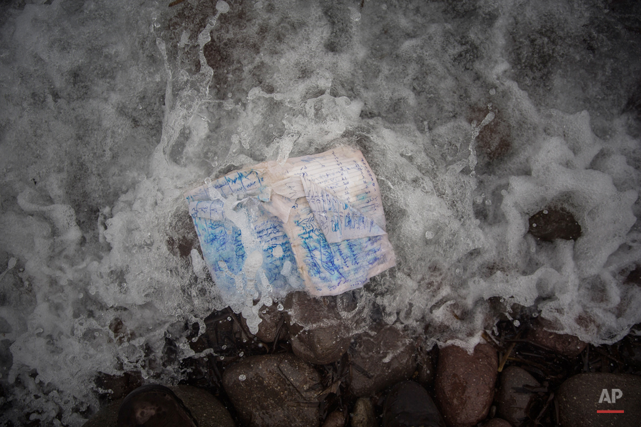 In this Thursday, Oct. 8, 2015 photo, a notebook with notes and drawings is placed to be portrayed a few cm from the place where it was found on a beach next to the town of Skala Sikaminias, on the northeastern Greek island of Lesbos. (AP Photo/Santi Palacios)