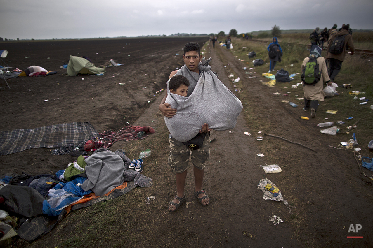 """In this photo taken on Friday, Sept. 11, 2015, Syrian refugee Hussein Sbaih, 18, who came from Damascus, Syria, carries his cousin Saifuallah, 7, whose legs are broken, while posing for a picture after they crossed the Serbian-Hungarian border near Roszke, southern Hungary. """"My cousin's legs are broken and I had to carry him for long distances I am so tired and lost and have no clue where we are going,"""" Sbaih said. (AP Photo/Muhammed Muheisen)"""